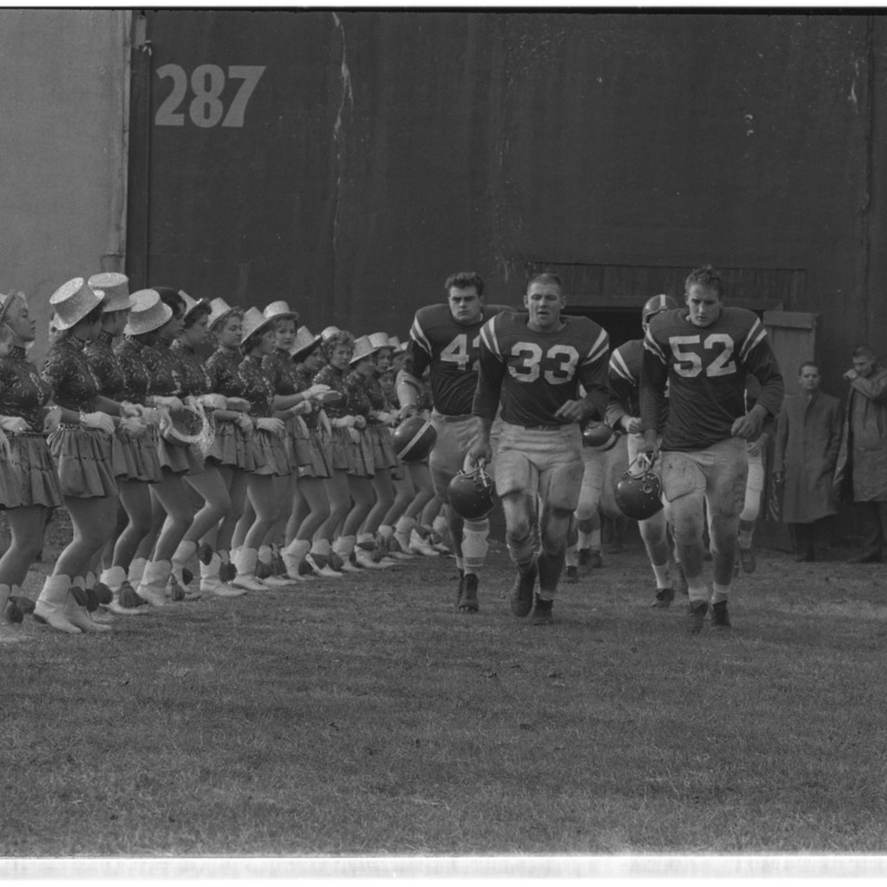Football players enter stadium, running past Sparkettes