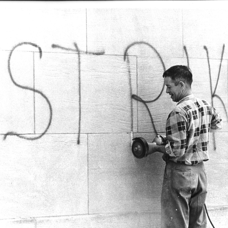 "Employee cleaning ""Strike"" graffiti"